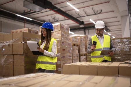 Warehouse workers using bar code scanner and tablet and checking goods inventory.